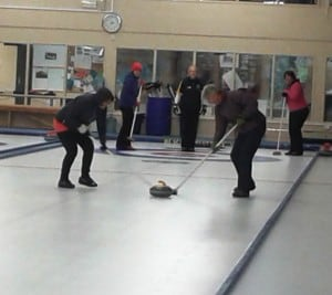 Frantically sweeping the ice to make the curling iron go faster!
